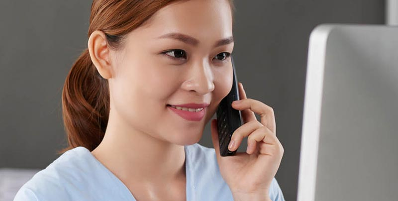 Asian nurse on the phone looking at her computer